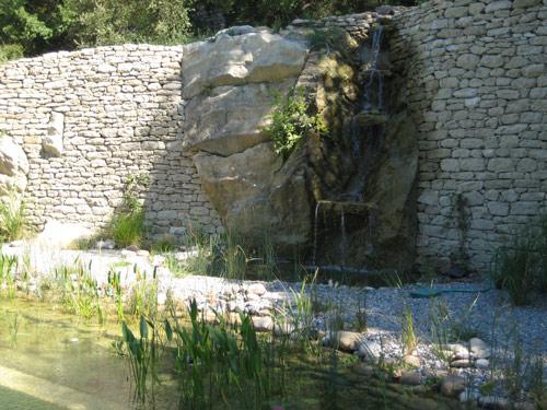 cascade rocheuse d'aspect naturel au pied d'un bassin dans jardin aquatique